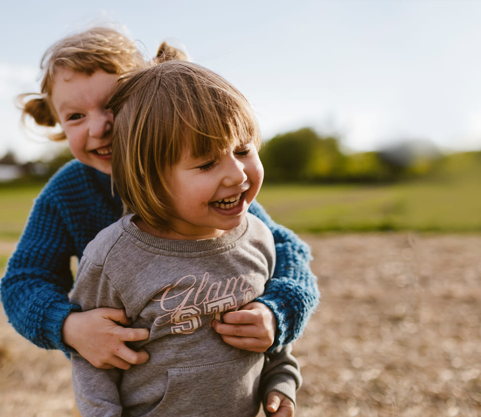 Close-up shot of two toddlers embracing while playing in an open field.