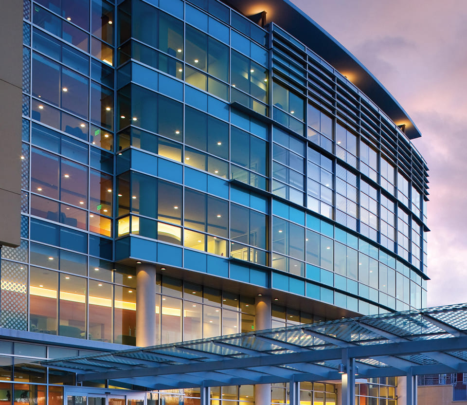 Angled view of a glass-front building with beautiful sunset lighting bouncing off the windows.